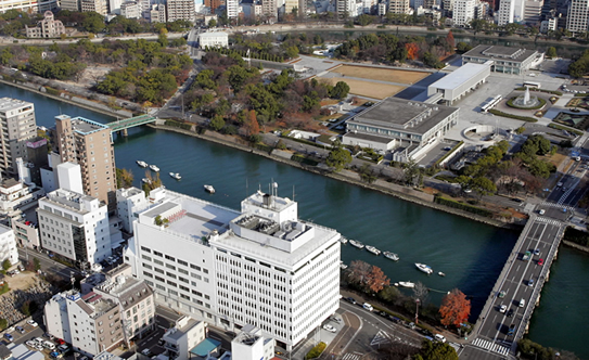 The Chugoku Shimbun building (the white building in the foreground) stands across the river from Peace Memorial Park.